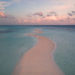 Sand beach by sea on Maledives during sunset captured by a drone