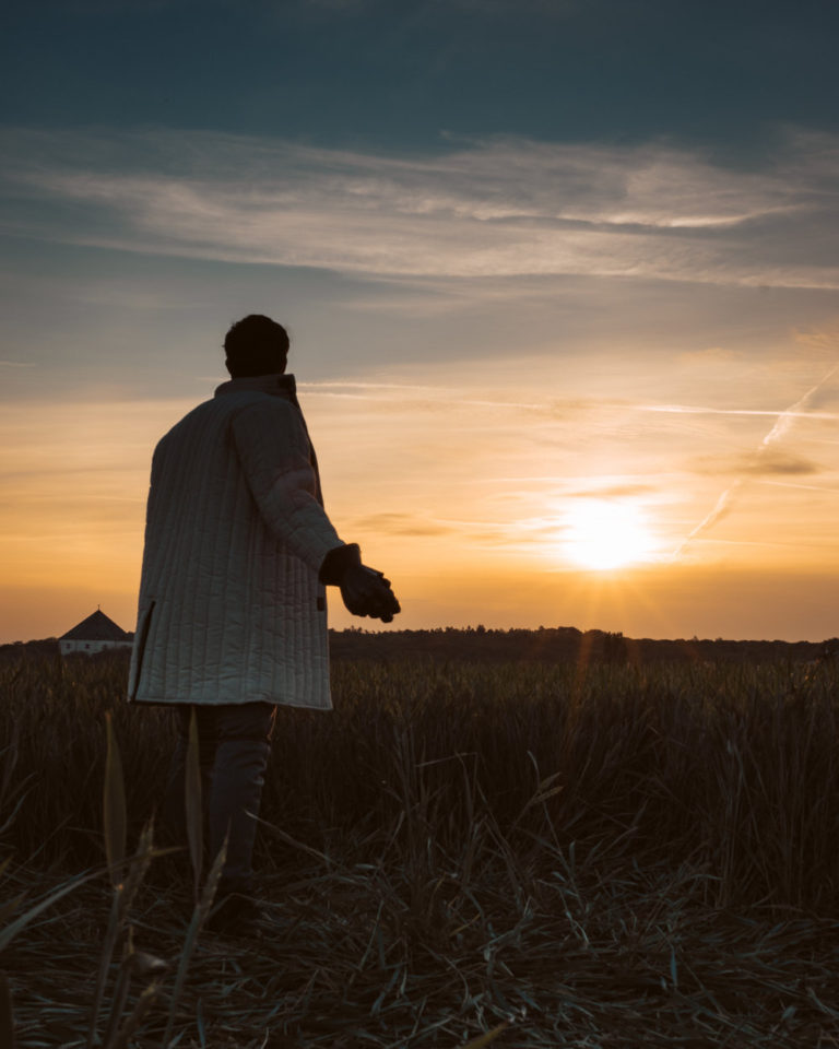 Portrait photography of Knight on Trip standing in grass field near Bila Hora during sunset