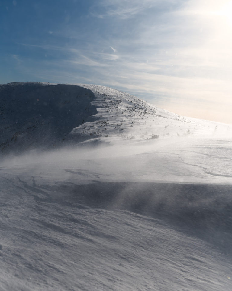 Hiking photo of strong wind breeze on snowy mountain Sněžka