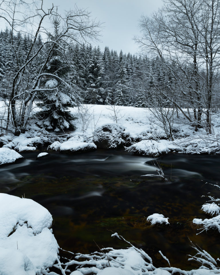 River and snowy landscape view in Jizera Mountains