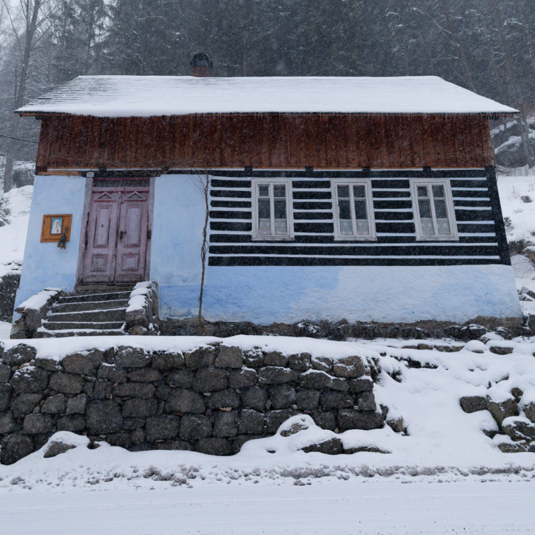 Snowflakes and snowy old cottage view in Jizera Mountains
