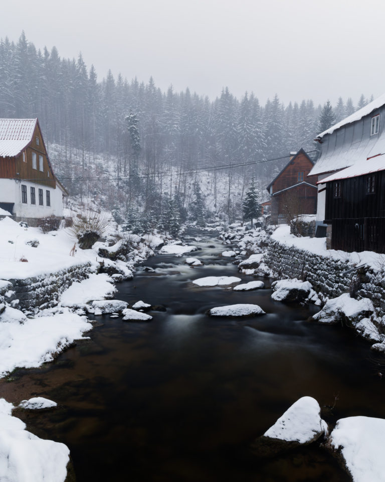 River and snowy town view in Jizera Mountains